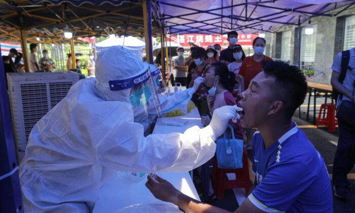 Un hombre recibe una prueba de ácido nucleico para el COVID-19 en Guangzhou, una ciudad de la provincia de Guangdong, en el sur de China, el 30 de mayo de 2021. (STR/AFP vía Getty Images)