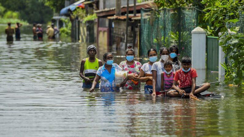 Los residentes se abren paso a través de las aguas de las inundaciones tras las fuertes lluvias monzónicas en Kelaniya, en las afueras de Colombo, Sri Lanka, el 6 de junio de 2021. (Ishara S. Kodikara/AFP vía Getty Images)