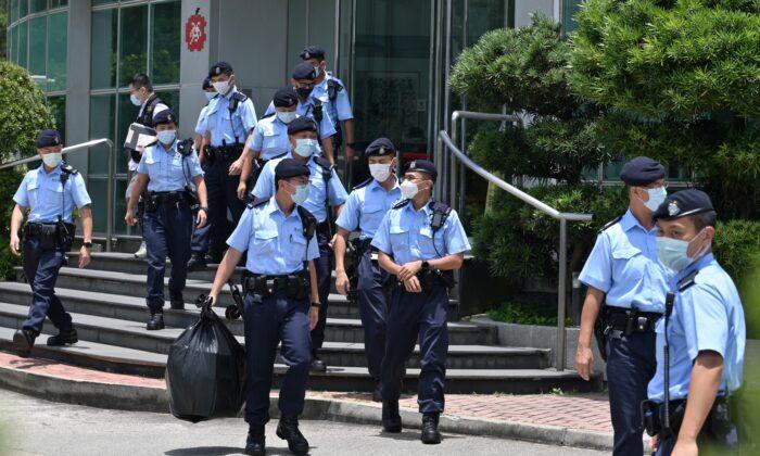 Unos agentes de policía abandonan las oficinas del periódico Apple Daily en Hong Kong tras una redada realizada por más de 500 agentes el 17 de junio de 2021. (Anthony Wallace/AFP vía Getty Images)