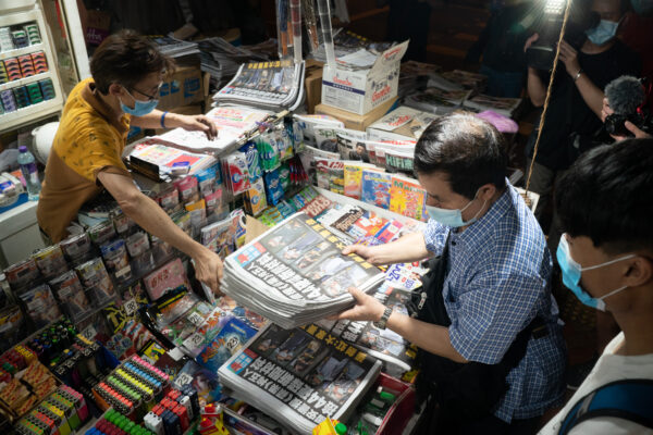 Un hombre compra varios ejemplares del último número de Apple Daily en Hong Kong el 18 de junio de 2021. (Anthony Kwan/Getty Images)