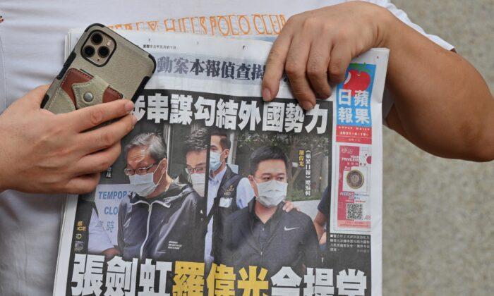 Un manifestante en apoyo de dos ejecutivos del medio de prensa prodemocrático de Hong Kong Apple Daily, el editor jefe Ryan Law y el director general Cheung Kim-hung, sostiene un ejemplar del periódico durante una protesta frente al tribunal en Hong Kong el 19 de junio de 2021. (Peter Parks/AFP vía Getty Images)