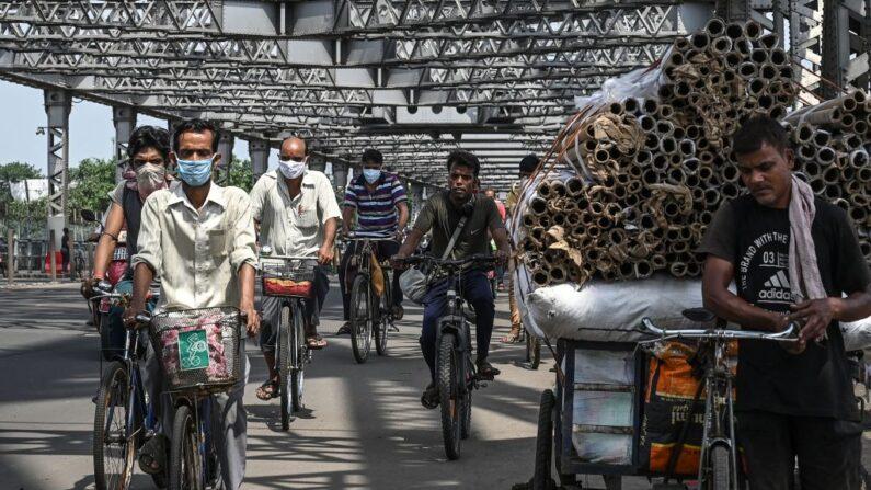 Los transeúntes cruzan el puente de Howrah en sus bicicletas mientras el gobierno estatal suspende el transporte público regular durante el bloqueo impuesto para frenar la propagación del covid-19, en Calcuta (India) el 23 de junio de 2021. (Dibyangshu Sarkar / AFP vía Getty Images)