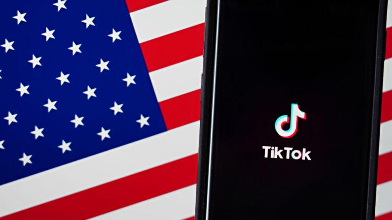 En esta ilustración fotográfica, se muestra un teléfono móvil con la aplicación TikTok, junto a la bandera estadounidense, el 3 de agosto de 2020 en la ciudad de Nueva York. (Cindy Ord/Getty Images)
