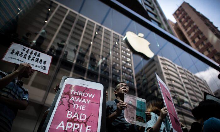Defensores de derechos humanos organizan una protesta durante el lanzamiento del iPhone 6s frente a una tienda Apple en Hong Kong, el 25 de septiembre de 2015. Los defensores de derechos dijeron que un proveedor chino de vidrio, para pantalla táctil del gigante de los teléfonos inteligentes, estaba explotando a sus trabajadores. (Philippe Lopez/AFP a través de Getty Images)