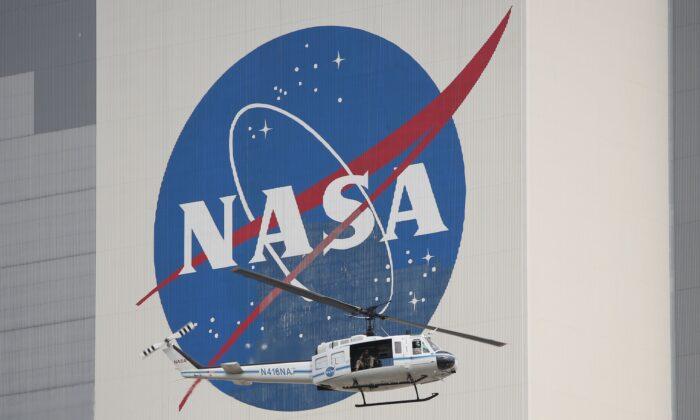 Un helicóptero de seguridad de la NASA sobrevuela el edificio de ensamblaje de vehículos en el Centro Espacial Kennedy, en Florida, el 26 de mayo de 2020. (GREGG NEWTON/AFP a través de Getty Images)