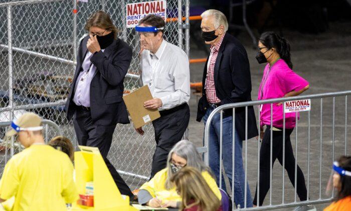 Exsecretario de Estado Ken Bennett (2do-iz) mueve las boletas durante una auditoría electoral en el Veterans Memorial Coliseum en Phoenix, Arizona, el 1 de mayo de 2021. (Courtney Pedroza/Getty Images)