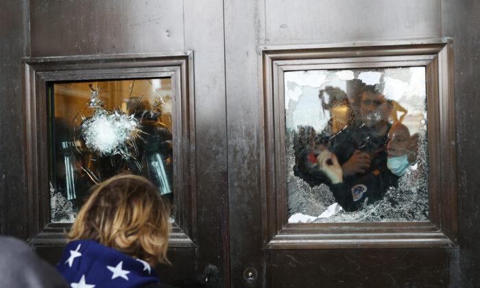 Un policía del Capitolio mira por una ventana rota mientras una multitud intenta entrar en el Capitolio de Estados Unidos, en Washington el 6 de enero de 2021. (Tasos Katopodis/Getty Images)