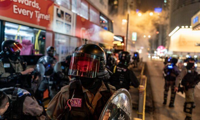 La policía antidisturbios reacciona tras disparar gases lacrimógenos para dispersar a los manifestantes en Hong Kong, China, el 24 de diciembre de 2019. (Anthony Kwan/Getty Images)