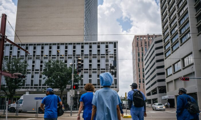 Trabajadores médicos y peatones cruzan una intersección fuera del Hospital Metodista de Houston, en Houston, Texas, el 9 de junio de 2021. (Brandon Bell/Getty Images)