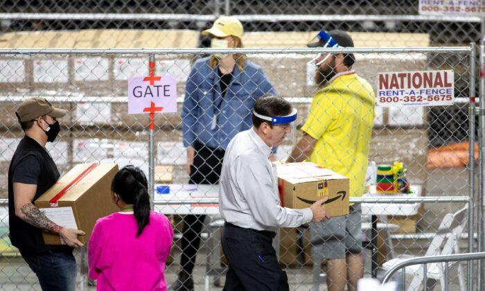 El exsecretario de Estado de Arizona, Ken Bennett, a la derecha, mueve las boletas de las elecciones generales de 2020 durante una auditoría en el Veterans Memorial Coliseum, en Phoenix, Arizona, el 1 de mayo de 2021. (Courtney Pedroza/Getty Images)