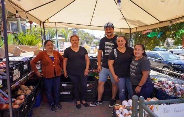 """El creador de la """"Mesa de justicia y esperanza"""", Christian Ramírez, junto a las voluntarias, las mexicanas Araceli Mora (2i) y Alma Alcantar (2d), y las guatemaltecas Ofelinda (i) y Marcela (d), frente a una mesa surtida de frutas, vegetales y algunas latas de alimentos el 5 de junio en el barrio de Sherman en San Diego, California. (Manuel Ocaño/EFE)"""