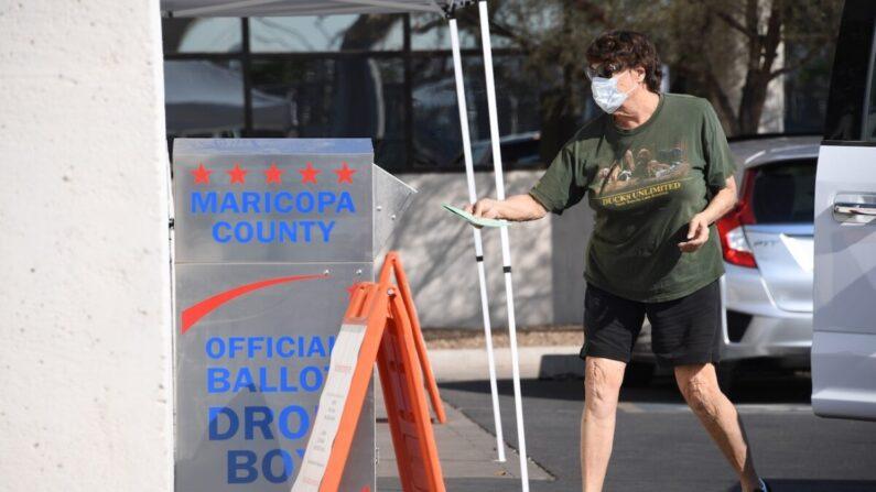 La gente deposita sus votos por correo para las elecciones presidenciales en un buzón de recolección de votos en Phoenix, Arizona, el 18 de octubre de 2020. (Robyn Beck/AFP vía Getty Images)