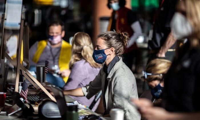 Trabajadores electorales registran a los votantes en un centro de votación el día de las elecciones en Denver, Colorado, el 3 de noviembre de 2020. (Chet Strange/AFP vía Getty Images)