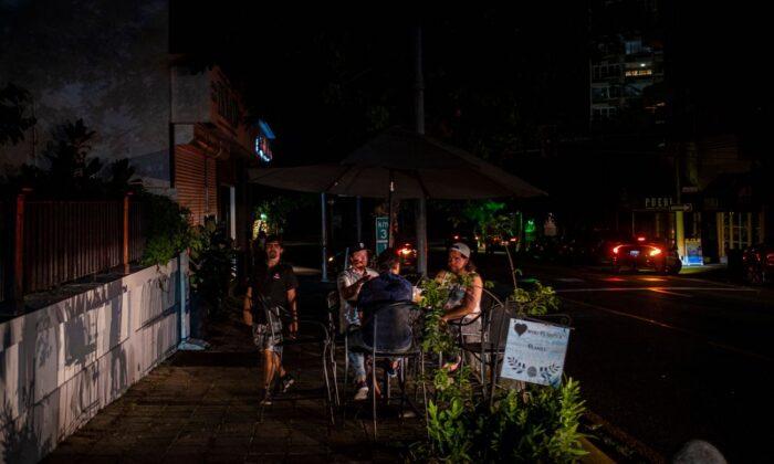 Unas personas fuera de un restaurante en una calle oscura y habitualmente concurrida en San Juan (Puerto Rico) el 10 de junio de 2021. (Ricardo Arguengo/AFP vía Getty Images)