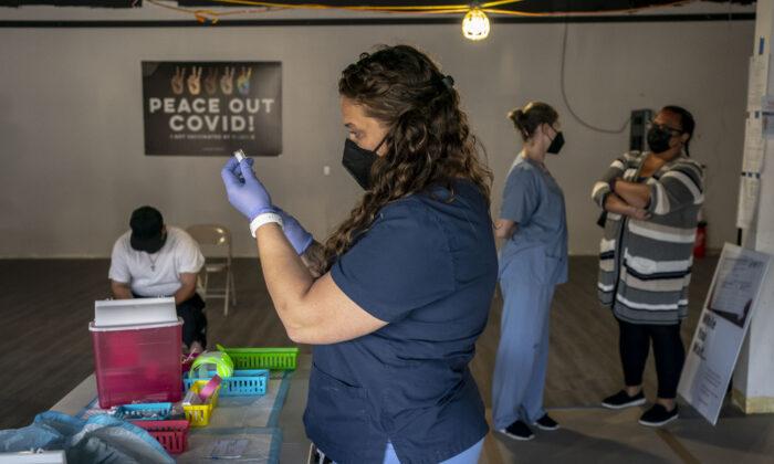 La enfermera, Nicole Warner, prepara dosis de la vacuna anti-COVID durante la jornada de vacunación Joints4Jabs COVID-19, en la tienda de cannabis Uncle Ikes White Center, en Seattle, Washington, el 16 de junio de 2021. (David Ryder/Getty Images)
