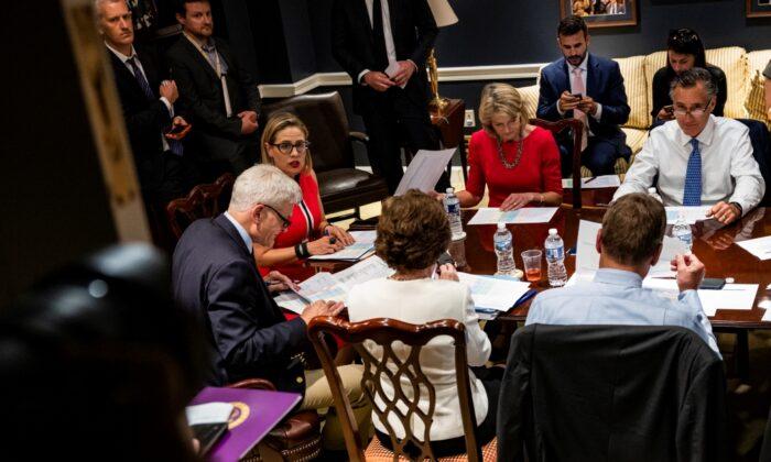 De izquierda a derecha: El senador Bill Cassidy (R-LA.), la senadora Kyrsten Sinema (D-AZ.), la senadora Lisa Murkowski (R-AK.) y el senador Mitt Romney (R-UT.) celebran una reunión bipartidista sobre las infraestructuras en el sótano del Capitolio de EE. UU. el 8 de junio de 2021. (Samuel Corum/Getty Images)