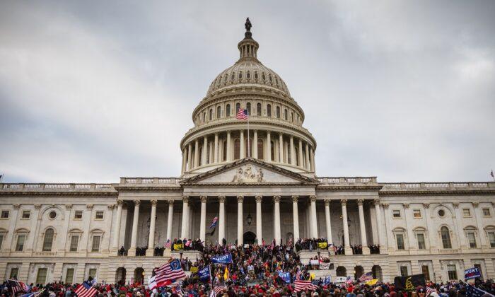 Un gran grupo de manifestantes se para en los escalones del edificio del Capitolio, en Washington, el 6 de enero de 2021. (Jon Cherry/Getty Images)