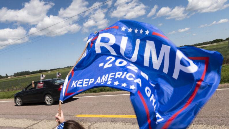 Los partidarios de Trump ondean banderas fuera del Aeropuerto Regional de Mankato mientras el presidente Donald Trump hace una parada de campaña en Mankato, Minnesota, el 17 de agosto de 2020. (Stephen Maturen/Getty Images)