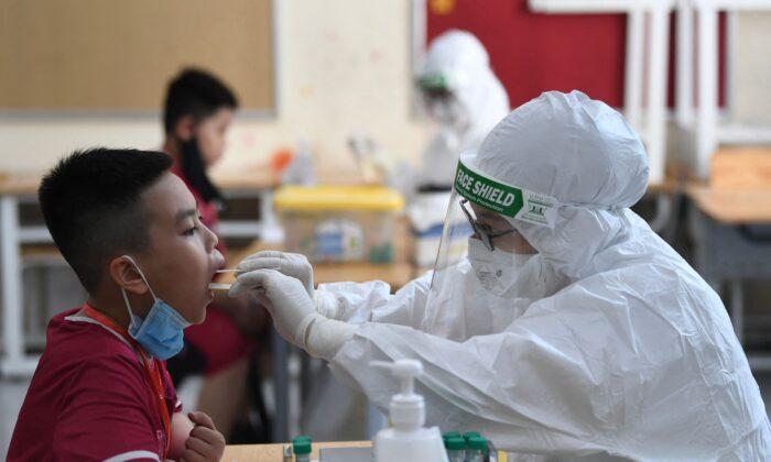 Un trabajador de la salud, que usa equipo de protección personal (EPP), realiza una prueba de COVID-19 en un estudiante de la escuela privada Vinschool, en Hanoi, Vietnam, el 22 de mayo de 2021. (Nhac Nguyen/AFP a través de Getty Images)
