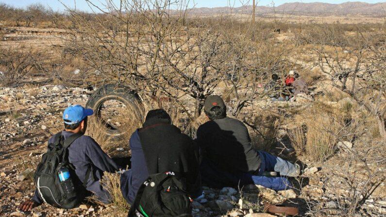 Inmigrantes mexicanos descansan detrás de unos arbustos en el desierto de Arizona, cerca de Sasabe, estado de Sonora, durante un intento de cruzar ilegalmente la frontera entre Estados Unidos y México, el 6 de abril de 2006. (Omar Torres/AFP/Getty Images)