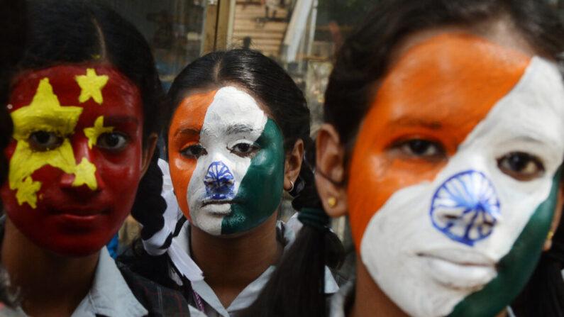 Estudiantes de escuelas de la India posan con la cara pintada con las banderas nacionales de India y China (I) en Chennai el 10 de octubre de 2019, antes de una cumbre entre el primer ministro indio, Narendra Modi y el líder chino Xi Jinping en la ciudad india de Chennai. (Arun Sankar / AFP a través de Getty Images)
