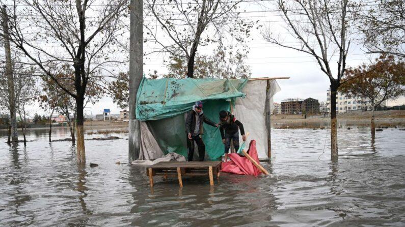 En una foto de archivo, vendedores de pie en su puesto en una calle inundada después de una fuerte lluvia en Kabul (Afganistán) el 15 de noviembre de 2020. (Wakil Kohsar/AFP vía Getty Images)