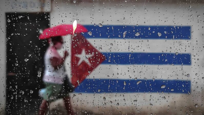 Una mujer camina cerca de un grafiti con la bandera cubana en La Habana el 12 de enero de 2021. (Yamil Lage/AFP vía Getty Images)