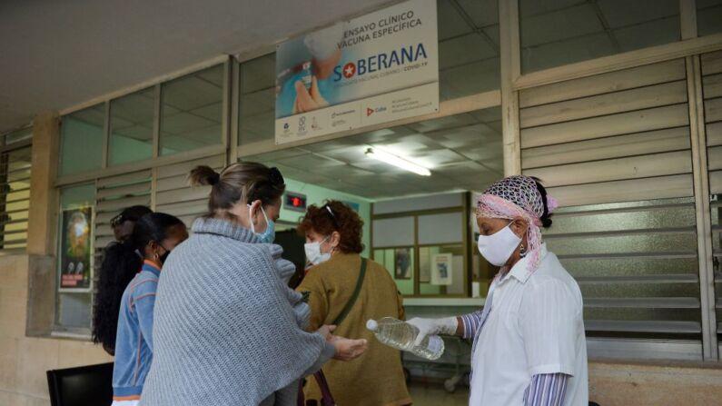 Una trabajadora de la salud aplica alcohol en gel a una mujer en una policlínica donde se lleva a cabo la fase II b del ensayo clínico del candidato a vacuna Soberana 02 contra el Covid-19, en La Habana, el 19 de enero de 2021. (Foto de YAMIL LAGE/AFP a través de Getty Images)