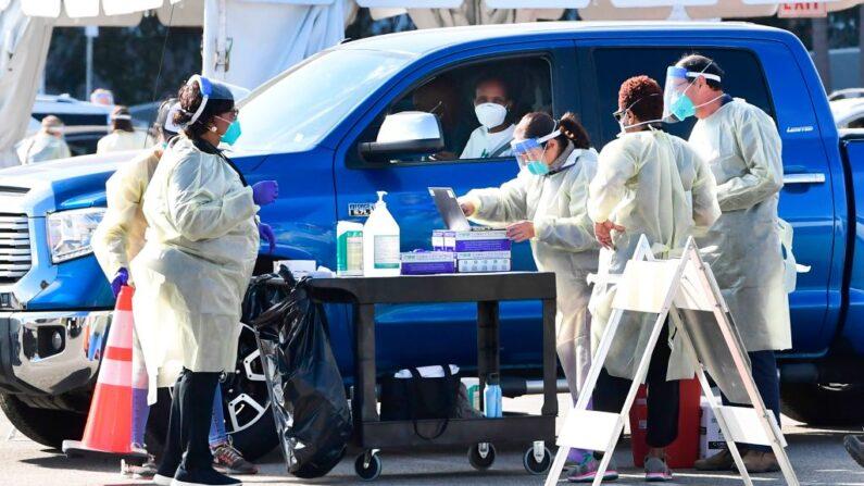La gente se acerca en sus vehículos para recibir las vacunas contra covid-19 en el aparcamiento de The Forum en Inglewood, California (EE.UU.), el 19 de enero de 2021. (Frederic J. Brown/AFP vía Getty Images)