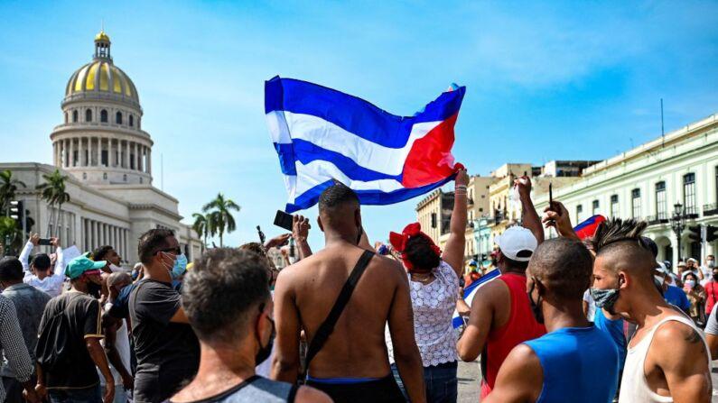"""Los cubanos se encuentran fuera del Capitolio de La Habana durante una manifestación contra el gobierno comunista cubano liderado por Miguel Díaz-Canel en La Habana, el 11 de julio de 2021. Miles de cubanos participaron marchando a través de la ciudad coreando """"Abajo la dictadura"""" y """"Queremos libertad"""". (Yamil Lage/AFP vía Getty Images)"""