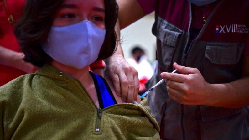Una menor de edad recibe una dosis de la vacuna Pfizer-BioNTech contra el COVID-19 en un centro de vacunación en Asunción (Paraguay), el 23 de julio de 2021. (Norberto Duarte/AFP vía Getty Images)