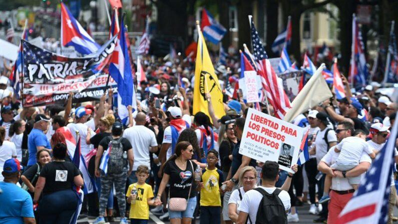Personas marchan durante una protesta contra el régimen de Cuba mientras la gente agita carteles y banderas cubanas cerca de la Casa Blanca en Washington DC, el 26 de julio de 2021. (Brendan Smialowski/AFP vía Getty Images)