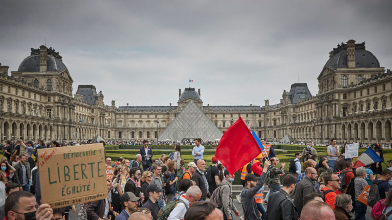 Manifestantes antivacunas marchan frente al Museo del Louvre mientras miles de personas salen a las calles de la capital francesa para protestar contra el nuevo pase de la vacuna COVID-19 anunciado por el presidente Macron, el 17 de julio de 2021 en París, Francia.(Kiran Ridley/Getty Images)