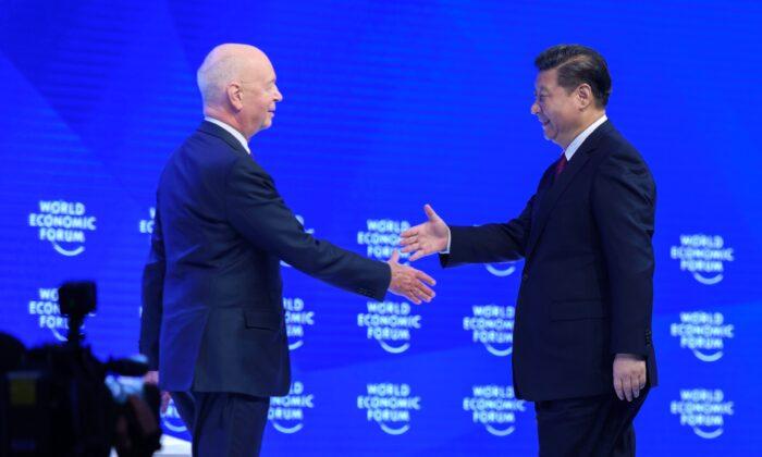 El líder chino Xi Jinping (Der.) estrecha la mano del fundador y presidente ejecutivo del Foro Económico Mundial, Klaus Schwab (Izq.), antes de pronunciar un discurso durante el primer día del FEM, el 17 de enero de 2017, en Davos. (Fabrice Coffrini/AFP a través de Getty Images)