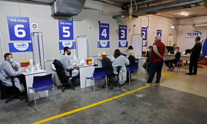 Trabajadores sanitarios del centro de vacunación Maccabi Health administran dosis de la vacuna anti-COVID de Pfizer-BioNtech dentro del estacionamiento del centro comercial Givatayim, en la ciudad costera mediterránea de Israel, Tel Aviv, el 26 de enero de 2021. (Jack Guez/AFP vía Getty Images)