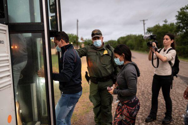 Inmigrantes ilegales suben a un autobús tras ser detenidos cerca de la frontera entre México y Estados Unidos en Del Río (Texas) el 16 de mayo de 2021. (Sergio Flores/AFP vía Getty Images)