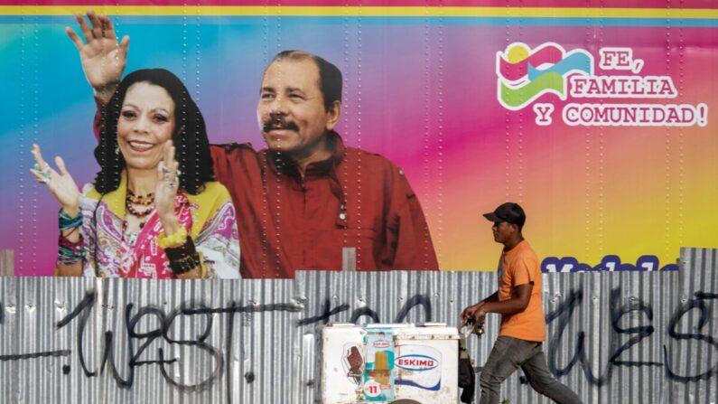 Un vendedor de helados camina junto a una clínica de salud móvil que muestra una imagen del dictador de Nicaragua Daniel Ortega (I) y su esposa la vicepresidenta Rosario Murillo (D) en Managua el 14 de abril de 2020. (INTI OCON/AFP vía Getty Images)
