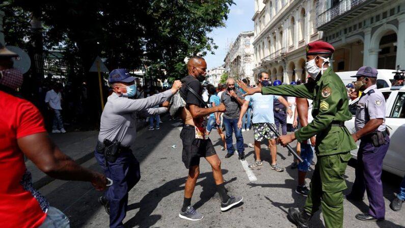 Policías arrestan a un hombre cuando personas se manifestaban el 11 de julio en una calle en La Habana (Cuba). EFE/Ernesto Mastrascusa