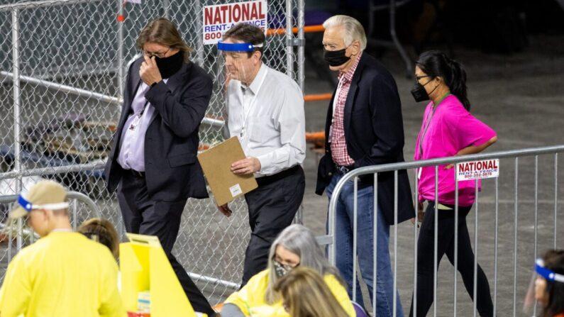 El exsecretario de Estado de Arizona Ken Bennett (segundo desde la izquierda) mueve las boletas durante una auditoría electoral en el Veterans Memorial Coliseum en Phoenix, Arizona, el 1 de mayo de 2021. (Courtney Pedroza/Getty Images)