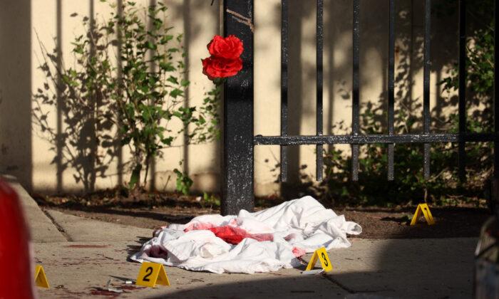 Una sábana empapada de sangre entre los marcadores de pruebas después de un tiroteo en el que tres personas fueron disparadas en el complejo de viviendas Wentworth Gardens en el barrio de Bridgeport en Chicago (Illinois) el 23 de junio de 2021. (Scott Olson/Getty Images)