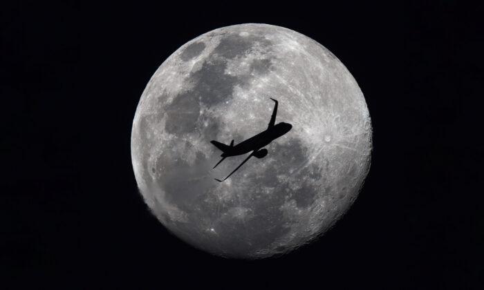 Fotógrafo capta accidentalmente a un avión de pasajeros volando frente a la luna de nieve