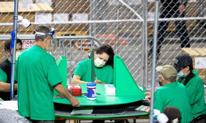 Contratistas que trabajan para la compañía Cyber Ninjas, designada por el Senado de Arizona, trabajan durante una auditoría electoral de 2020 en el Veterans Memorial Coliseum en Phoenix, Arizona, el 1 de mayo de 2021. (Courtney Pedroza/Getty Images)