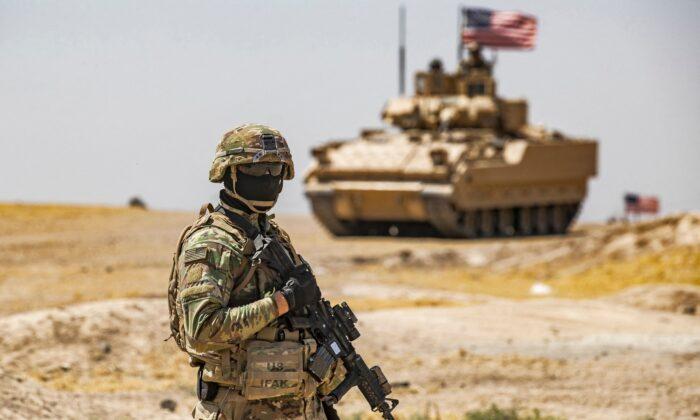 Un soldado de EE. UU. permanece cerca de un vehículo de combate Bradley (BFV) durante una maniobra de patrullaje cerca de los pozos petrolíferos de Rumaylan (Rmeilan) en la provincia nororiental siria de Hasakeh el 22 de junio de 2021. (Delil Soulieman/AFP vía Getty Images)