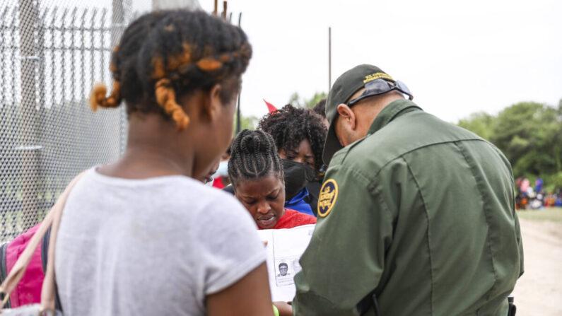 Un agente de la Patrulla Fronteriza comienza a organizar un grupo de más de 350 inmigrantes ilegales luego de que cruzaron el Río Bravo desde México a Del Rio, Texas, el 25 de julio de 2021. (Charlotte Cuthbertson/The Epoch Times)