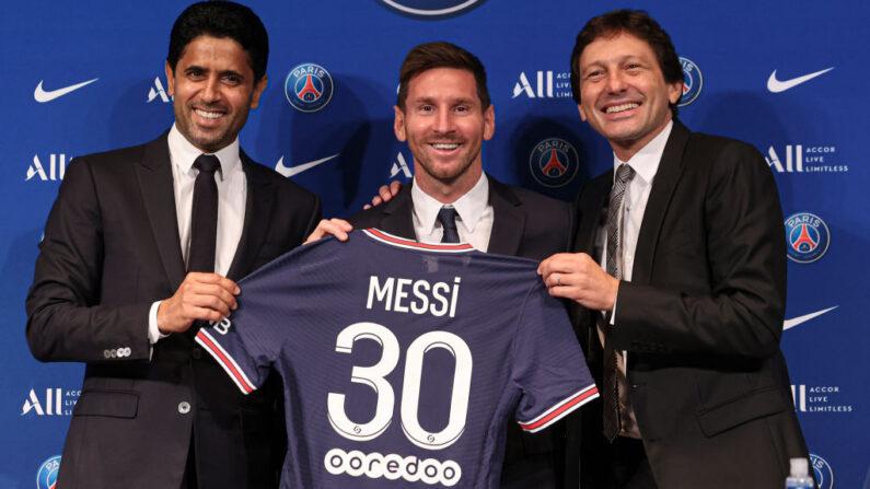 Lionel Messi posa con su camiseta junto al presidente Nasser Al Khelaifi (i) y Leonardo (d) tras la rueda de prensa del París Saint-Germain en el Parque de los Príncipes el 11 de agosto de 2021 en París, Francia. (Sebastien Muylaert/Getty Images)