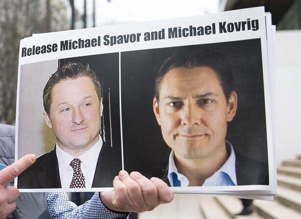 Louis Huang, de Vancouver Freedom and Democracy for China, sostiene fotos de los canadienses Michael Spavor y Michael Kovrig, detenidos por China, frente a la Corte Suprema de Columbia Británica, en Vancouver, el 6 de marzo de 2019, (JASON REDMOND/AFP vía Getty Images)