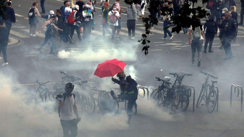 Un manifestante patea un proyectil de gas lacrimógeno en el día nacional contra la vacunación obligatoria anti-COVID y contra el uso obligatorio del pase de salud solicitado por el gobierno francés, en París, el 31 de julio de 2021. (GEOFFROY VAN DER HASSELT/AFP a través de Getty Images)