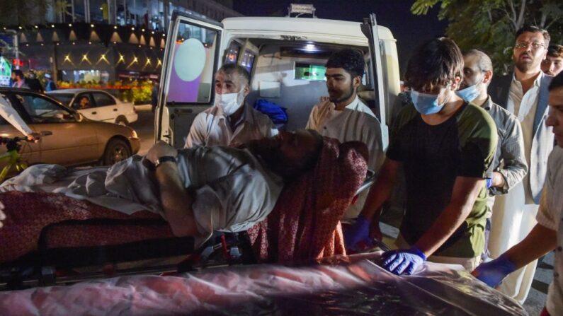 Voluntarios y personal médico traen a un hombre herido para su tratamiento después de dos potentes explosiones, que mataron al menos a 15 personas, fuera del aeropuerto en Kabul (Afganistán), el 26 de agosto de 2021. (Wakil Kohsar/AFP vía Getty Images)