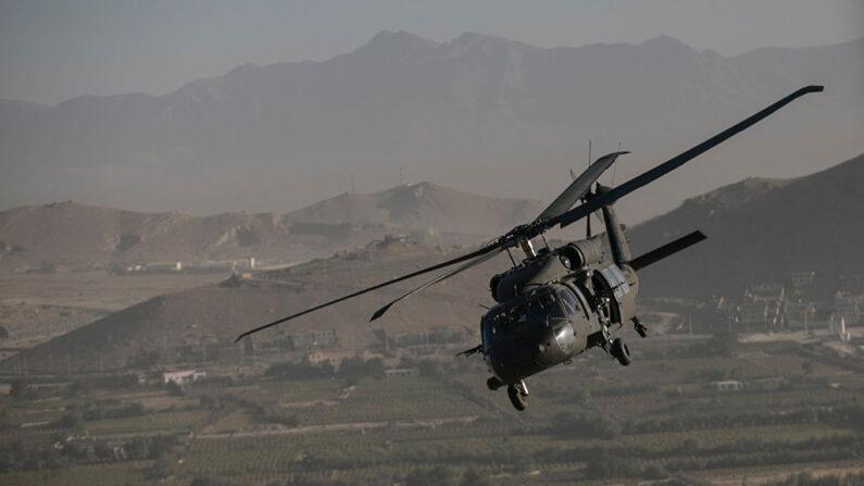 Un Black Hawk forma parte de un convoy de helicópteros que llevan a los medios de comunicación y al primer ministro británico David Cameron al Palacio Presidencial desde el aeropuerto de Kabul, el 3 de octubre de 2014 en Kabul, Afganistán. (Dan Kitwood - Pool/Getty Images)
