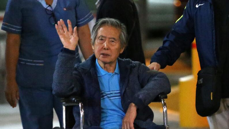 El expresidente de Perú Alberto Fujimori saluda a sus partidarios mientras es sacado en silla de ruedas de la Clínica Centenario en Lima (Perú) el 04 de enero de 2018. (Luka Gonzales/AFP vía Getty Images)